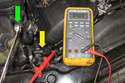 In this photo the wrench (green arrow) is away from the sensor (yellow arrow), so the DVOM reads 5 volts.