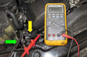 In this photo the wrench (green arrow) is close to the sensor (yellow arrow), so the DVOM reads 5 volts.
