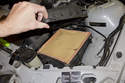 Once loose, lift and remove the air filter housing lid from the engine compartment.