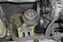 Working at the power steering reservoir, remove the two 10mm fasteners (green arrows).