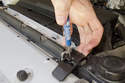 Working at top of radiator support, unlock the plastic radiator mount by inserting a small flathead screwdriver, then press screwdriver down while lifting up on mount and pulling it toward front bumper.