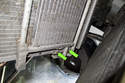 Lift the radiator up slightly to expose the lower fasteners on the power steering cooler.