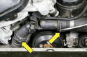 Working at both radiator hoses, use a flathead screwdriver to lever out the coolant hose retaining clips (yellow arrow).