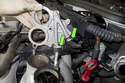 Lift up the crankcase breather air plate and remove both coolant hoses.