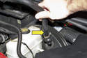 Working at brake booster, remove brake booster vacuum hose (yellow arrow) by pulling straight out of brake booster.