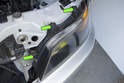 Remove the three 8mm headlight mounting fasteners (green arrows).