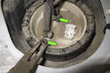 Using a pair of needle nose pliers, pull the plastic caps (green arrows) off the fuel line clamps (if equipped).