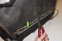 Working at the bottom of the seat back, remove the plastic trim clip.