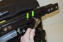 Working at the front bottom of the seal rail, remove two T25 Torx fasteners (green arrows).