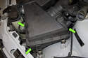 Next, you will unclip the three air filter housing retaining clips (green arrows).