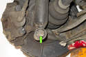 Remove rear shock 18mm mounting fastener (green arrow).