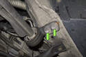 Working at rear of front control arm, remove two 17mm control arm bushing fasteners (green arrows).