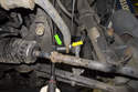 Working at the stabilizer bar, loosen the 16mm end link nut (green arrow) while counter-holding the 16mm boss on the link (yellow arrow).