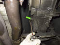 Using a fluid pump, fill transmission until fluid flows out of fill plug hole (green arrow).