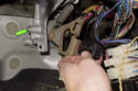Replacing brake light switch-Once the fastener (green arrow) is removed from bracket (loosened); remove the bracket with the brake light switch from the vehicle.