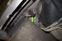 Next, working at the rear of the exhaust, locate the rubber insulator at the right side of the muffler (green arrow).