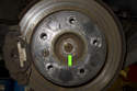 Remove center cap on rear wheel of vehicle.