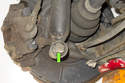 Working at back of trailing arm, remove the 18mm rear shock mounting fastener (green arrow).