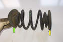 Install upper (yellow arrow) and lower (green arrow) spring pads onto new coil spring.