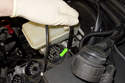 Using an 11mm line wrench, loosen the rear brake line (green arrow).