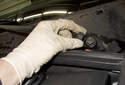 Open the hood, then remove the wiper arm nut trim cap.