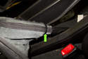 Working back at the parking brake lever, cut the tie strap (green arrow) off the trim boot.