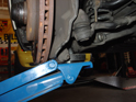 Place a floor jack under the front control arm as shown here.