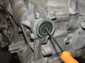 Use a pick tool to poke a hole in the center of the camshaft end cover and then pull it out.