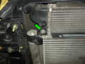Remove the 10mm bolt securing the left side of the A/C condenser to the radiator frame (green arrow).