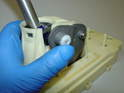 Place the bushing inside the metal carrier and over the small blue pivot point.