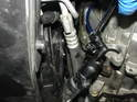 With the steering wheel puller still compressing the slave cylinder, attach a hose to the bleeder valve.