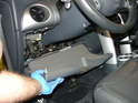 Remove the driver's side lower bolster panel by prying it off along the top edge and carefully remove it.