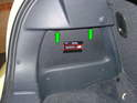 Press down on the two tabs (green arrows) to remove the access covers on both sides of the trunk compartment.