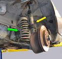 An examination of the suspension shows that the dust protector is almost completely missing (yellow arrow), the bump stop is almost shot, and the strut is leaking.