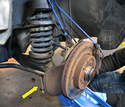 Insert the compressor strut through the hole in the lower control arm and feed it through the plates.