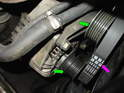 Route the new belt (purple arrow) over the various pullies on the engine (green arrows).