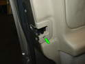 Remove the screw holding the door latch cover in place (green arrow).