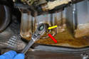 On the rear of the oil pan you will find the 13mm drain plug (red arrow), use a wrench and remove it.