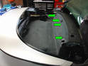 3:: Pry out the four black plastic tabs holding the upper part of the carpeting to the roll bar bulkhead (green arrows).